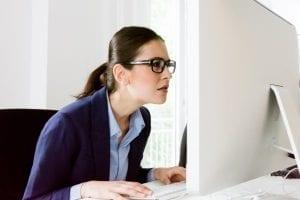 Woman squinting at a computer screen
