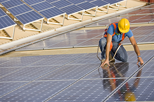 image of worker installing photovoltaic solar panel