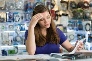Young white woman working in computer shop, checking bills and invoices with worried expression
