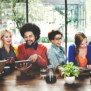 Happy young people sitting at a table reading a tablet