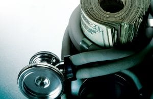 Stethoscope wrapped around a roll of twenty dollar bills