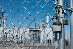 Padlock on a chain link fence with factory after layoff notices in the background