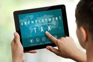Image of man using a tablet with the words 'unemployment tax' on the screen