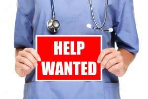 Medical professional holding a help wanted sign