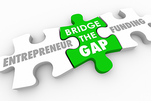 """Three jigsaw puzzle pieces with one in the middle labeled """"bridge the gap"""" connecting """"entrepreneur"""" and """"funding"""""""