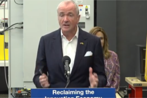 Phil Murphy gestures at the podium during a press conference on incentive programs.