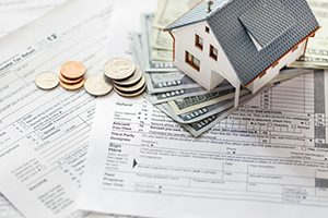 miniature house, $100 dollar bills and US coin sitting on top of a blank tax return form