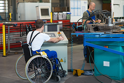 photo of disabled worker in wheelchair in factory on the machine
