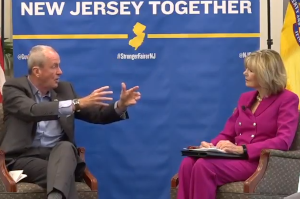 Gov. Phil Murphy sitting onstage Linda Bowden, chair of the New Jersey State Chamber of Commerce.