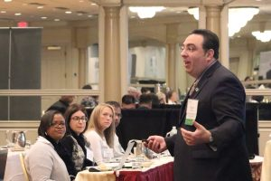 Michael Shadiack makes a point about job descriptions as seminar attendees watch and listen