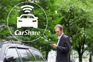 Man looking at is phone with an info bubble showing a car share graphic.