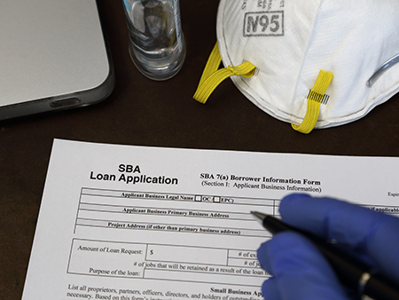 A rubber gloved hand is shown about to fill out a Small Business Administration aka SBA loan application form, with an N95 respirator dust mask and antibacterial gel nearby.