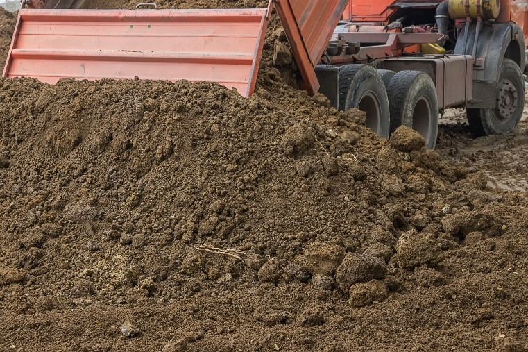 Dump truck unloading soil. View from the back of the truck with the soil spilling out of the bed.