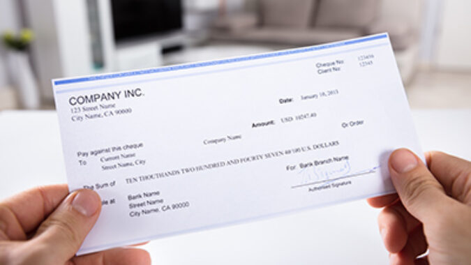 image of person holding a bank check