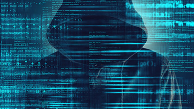 image of Cybersecurity, computer hacker with hoodie and obscured face, computer code overlaying image