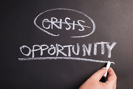 the words crisis and opportunity written on chalkboard