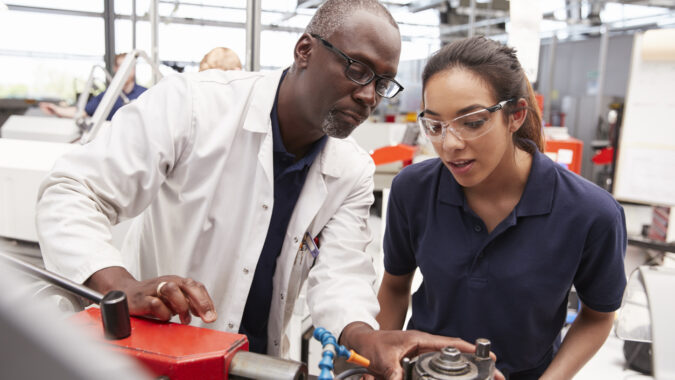 Young woman receives instruction as she works on technical equipment