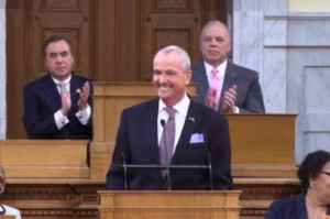Gov. Phil Murphy delivers his FY 2021 budget address. Behind him, Assembly Speaker Craig Coughlin and Senate President Steve Sweeney applaud..