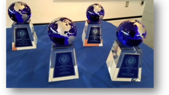 Trophies with planet earth perched on a base are arranged on a table.