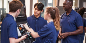 student apprentices receiving instruction on using a high-tech machinery in a shop