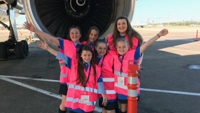 Five school girls and one adult wearing pink safety vests standing in front of a commercial airplane's jet engine on the tarmac
