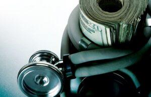 Stethoscope wrapped around a wad of $20 bills