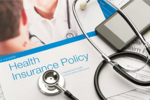 Stethoscope lying on top of a health insurance policy brochure