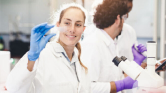 Woman in lab coat looking at a microscope slide