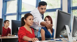 Guy teaching two women on a computer