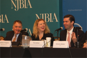 Governor Murphy's key advisors (from left): Chief of Staff Peter Cammarano, Chief Policy Advisor Kathleen Frangione, and Tim Sullivan, CEO of the New Jersey Economic Development Authority at a microphone-covered table and sharing a light moment during panel discussion