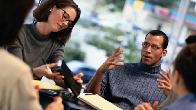 African American man in turtle neck leading a meeting of engaged colleagues