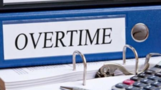 Blue binder labeled Overtime sitting on a desk