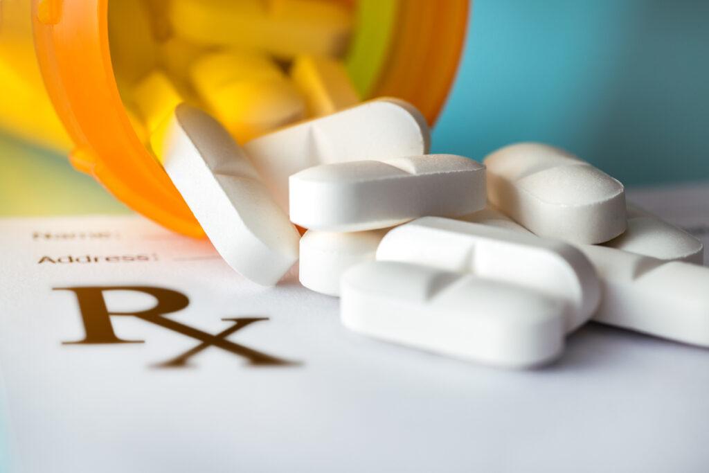 Prescription pills spilling out of a pill bottle near an Rx sign.