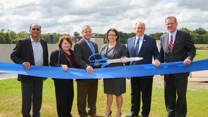 American Water Officials standing behind a blue ribbon holding a big pair of scissors