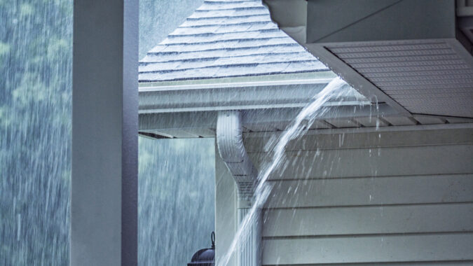 Rain storm water is gushing and splashing off the tile shingle roof - pouring over the overhanging eaves trough aluminum roof gutter system on a suburban residential colonial style house near Rochester, New York State, USA during a torrential July mid summer downpour.