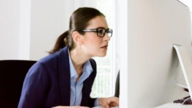Woman squinting at computer screen