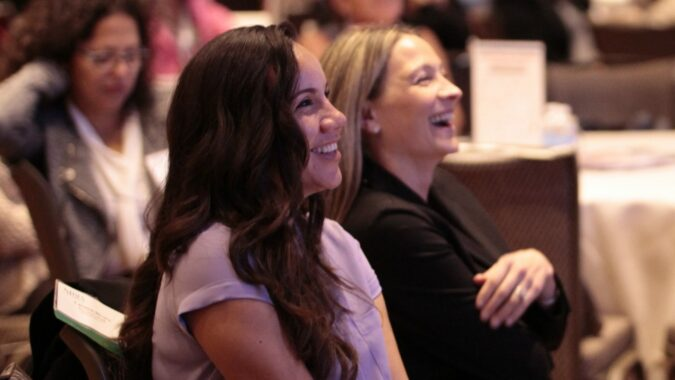 Two young women laughing in the audience at the Women Business Leaders Forum.