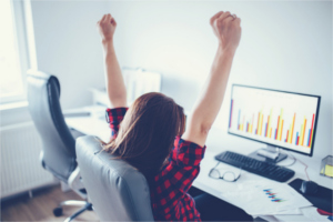 Woman sitting in front of computer with her arms raised in triumph