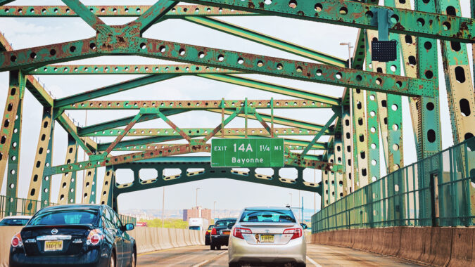 Car driving over a bridge with a NJ exit sign visible