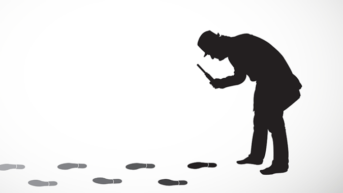 Silhouette of detective with magnifying glass following footprints.