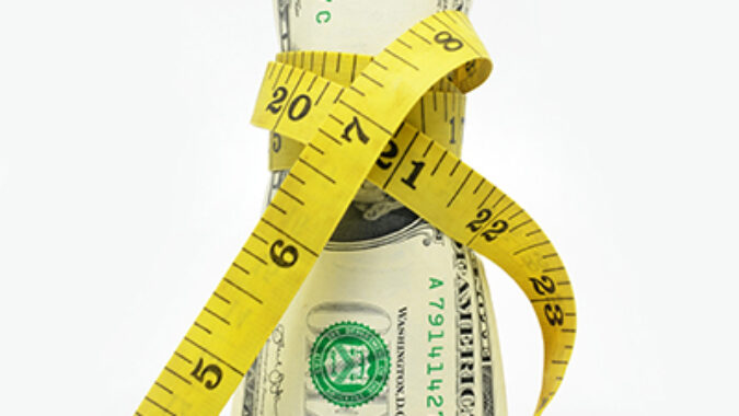 image of dollar bill being squeezed by tape measure