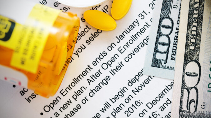 Open pill bottle next to $100 bill on top of open enrollment clause.