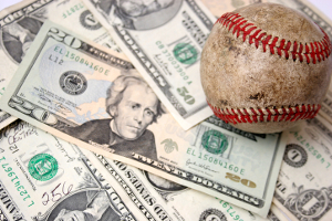 Photo if a baseball laying on top of U.S. cash