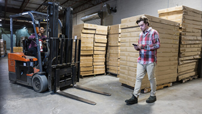 An accident waiting to happen. An industrial worker using a cell phone in a warehouse or factory walks in front of a forklift as it comes around a blind corner.