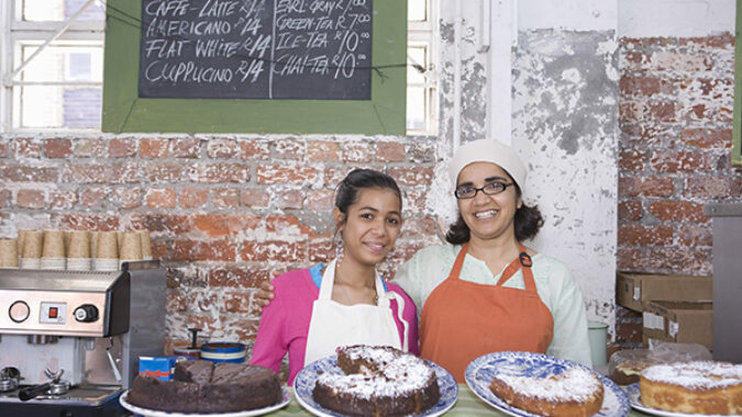 Portrait of happy mother and daughter in aprons standing at cake shop counter