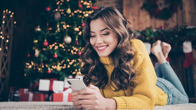 Young woman in front of Christmas tree shopping on her cell phone