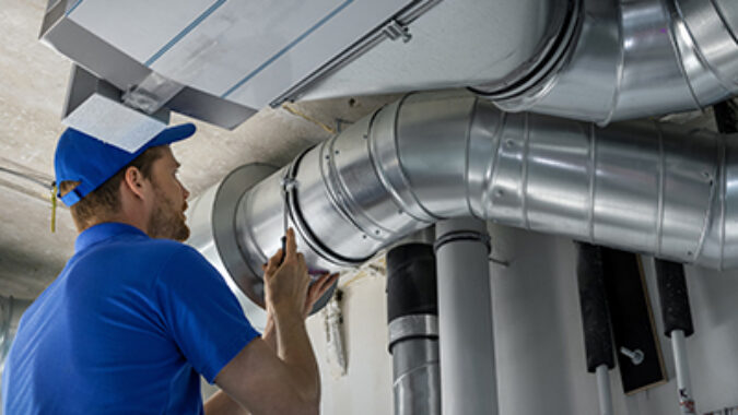hvac worker install ducted pipe system